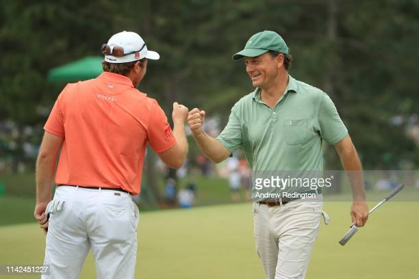 Eddie Pepperell of England fist bumps marker Jeff Knox on the 18th green during the third round of the Masters at Augusta National Golf Club on April...