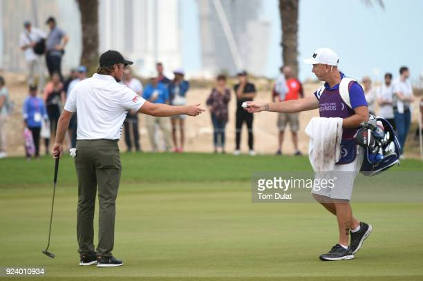Eddie Pepperell of England is handed his ball by caddie Mick Doran on the 16th green during the final round of the Commercial Bank Qatar Masters at...