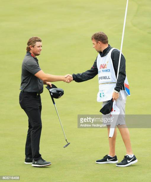 Eddie Pepperell of England shakes hands with caddie Jonathan Smart on the 18th green during day one of the HNA Open de France at Le Golf National on...