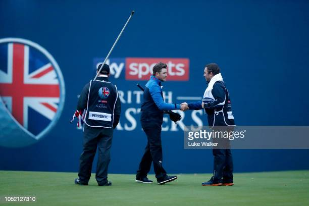 Eddie Pepperell of England shakes hands with Oliver Briggs Caddie of Alexander Bjork after finishing their round during day four of Sky Sports...