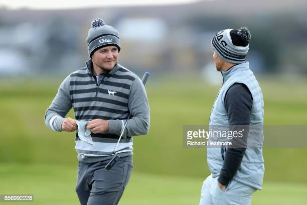 Eddie Pepperell of England speaks with Musician Dave Farrell during practice prior to the 2017 Alfred Dunhill Links Championship at The Old Course on...