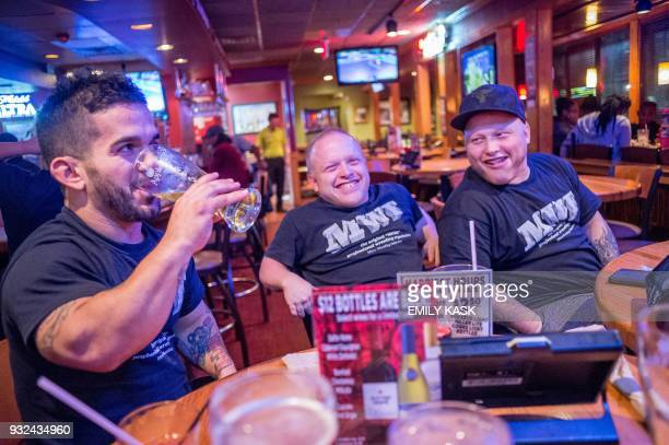 Eddie Piedra left Jamie Brooks center and Jacob Brooks right enjoy beers and food at Applebees with the rest of the team after their show in Laurel...