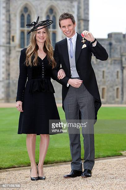 Eddie Redmayne poses with his wife Hannah after he was made an OBE by Queen Elizabeth II during an investiture ceremony at Windsor Castle on December...