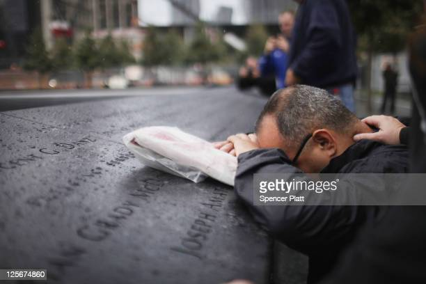 Eddie Reyes is comforted while remembering fifteen of his colleagues in the New York Police Department Emergency Service Unit who were killed on...