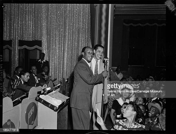 Eddie Rochester Anderson and Cab Calloway on stage with orchestra seated at music stands on left and audience on right in Hill City Auditorium...