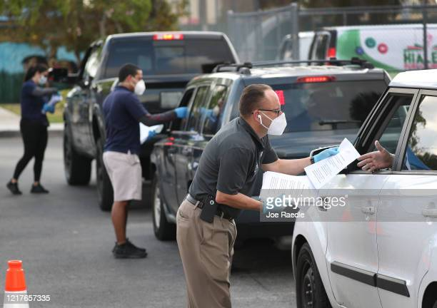 Eddie Rodriguez and other City of Hialeah employees hand out unemployment applications to people in their vehicles in front of the John F. Kennedy...