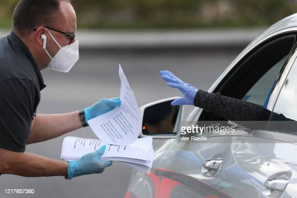 Eddie Rodriguez who works for the City of Hialeah hands out unemployment applications to people in their vehicles in front of the John F Kennedy...
