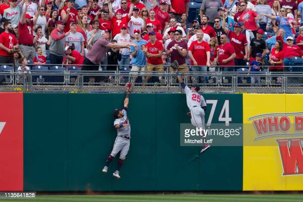 Eddie Rosario and Byron Buxton of the Minnesota Twins leap but cannot catch the two run home run ball hit by Rhys Hoskins of the Philadelphia...