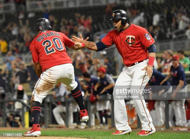Eddie Rosario and Nelson Cruz of the Minnesota Twins celebrate scoring runs against the Chicago White Sox during the twelfth inning of the game at...
