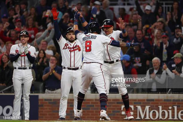 Eddie Rosario of the Atlanta Braves is congratulated by Ehire Adrianza and Travis d'Arnaud following a three run home run during the fourth inning of...