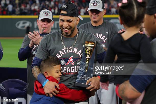 Eddie Rosario of the Atlanta Braves is hugged by his son after being named the Most Valuable Player of the National League Championship Series after...