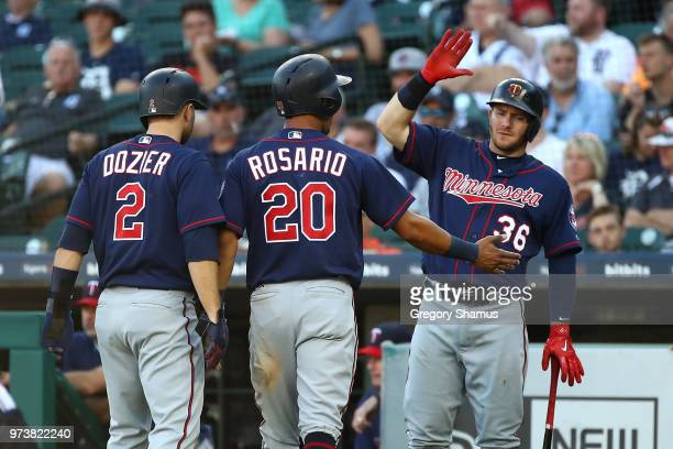 Eddie Rosario of the Minnesota Twins celebrates scoring a first inning run with Robbie Grossman and Brian Dozier while playing the Minnesota Twins at...