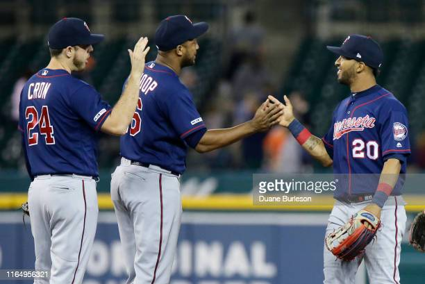 Eddie Rosario of the Minnesota Twins celebrates with C.J. Cron and Jonathan Schoop after a 13-5 win over the Detroit Tigers at Comerica Park on...