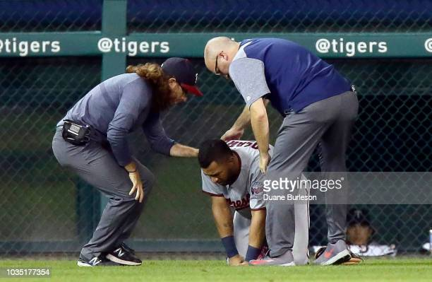 Eddie Rosario of the Minnesota Twins is assisted by trainers after injuring his lower right leg while fielding a ball hit by Jim Adduci of the...