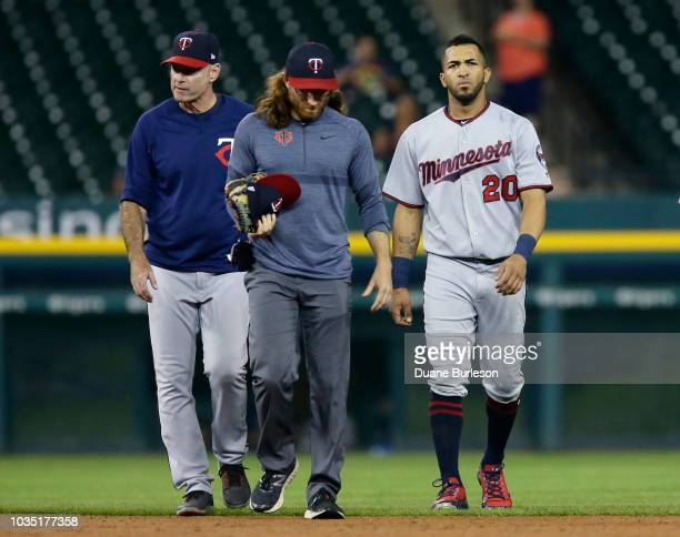 Eddie Rosario of the Minnesota Twins walks off with a trainer and manager Paul Molitor of the Minnesota Twins after injuring his lower right leg...