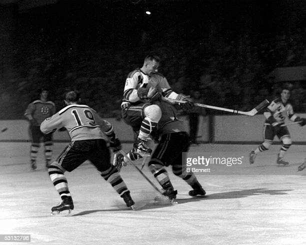 Eddie Shack of the New York Rangers leaps through the air between Doug Mohns and Fern Flaman of the Boston Bruins on January 14 1960 at the Boston...