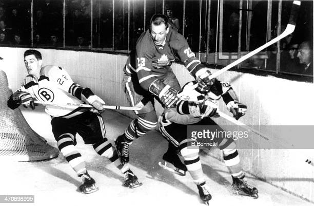 Eddie Shack of the Toronto Maple Leafs tries to get by JeanGuy Gendron of the Boston Bruins as Gendron's teammate Irvin Spencer skates away from the...