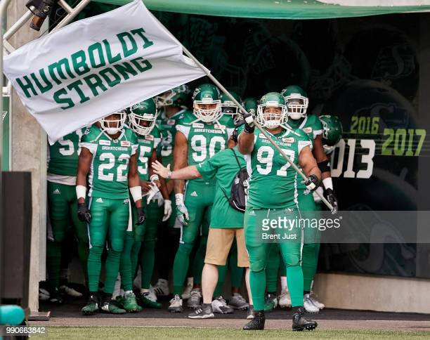 Eddie Steele of the Saskatchewan Roughriders waves a Humboldt Strong flag in tribute to the 16 members of the Humboldt Broncos hockey team killed in...