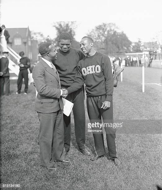 Eddie Tolan, great sprinter of a few years ago, congratulating Jesse Owens of Ohio State, after the latter had smashed three world's records, and...