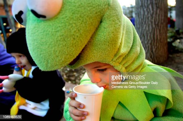 Eddie Voss of Boulder takes a sip of hot cider from BJ's Pizza Grill Brewery in his Kermit the Frog costume as his twoyearold brother Ryan Voss eats...