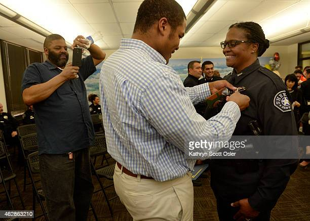 Eddie Yarbrough center pins a new sheriff badge on his mother recruit Dana Yarbrough as Dana's brother Robert Jackson gets a photo of the moment...