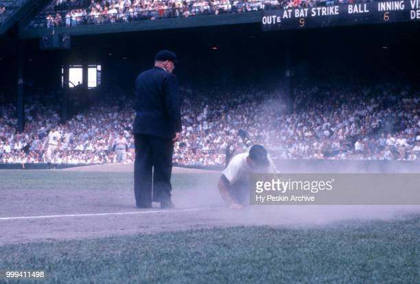 Eddie Yost of the Detroit Tigers collides with Vic Power of the Cleveland Indians as umpire Bill Summers is in position to make the call during an...