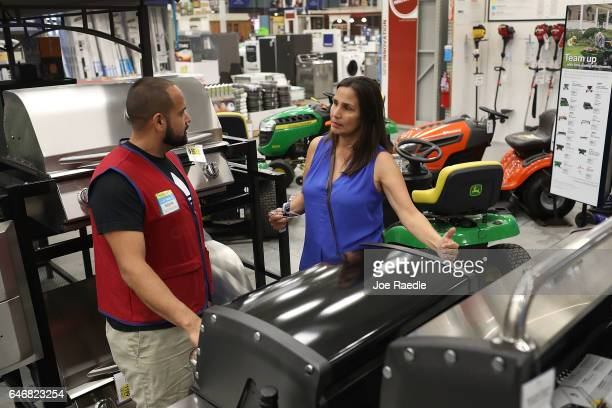 Eddie Zelaya helps Carmen Ledesma as she shops for a BBQ grill at the Lowe's store on the day the company reported a rise in earnings on March 1 2017...