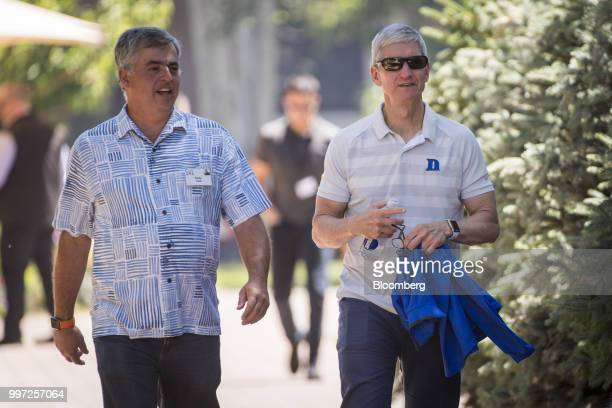 Eddy Cue senior vice president of internet software and services at Apple Inc left and Tim Cook chief executive officer of Apple Inc walk the grounds...