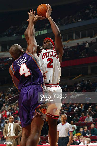 Eddy Curry of the Chicago Bulls shoots over Alton Ford of the Phoenix Suns during a game at the United Center on October 14 2002 in Chicago Illinois...