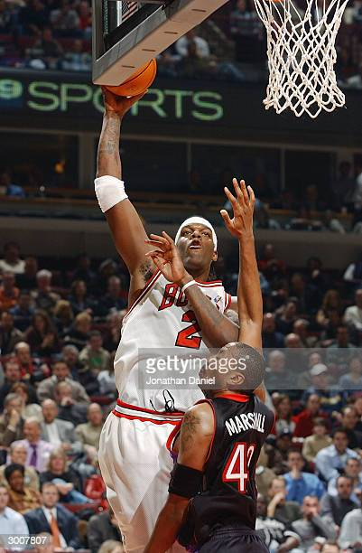 Eddy Curry of the Chicago Bulls shoots over Donyell Marshall of the Toronto Raptors during the game at United Center on February 17 2004 in Chicago...