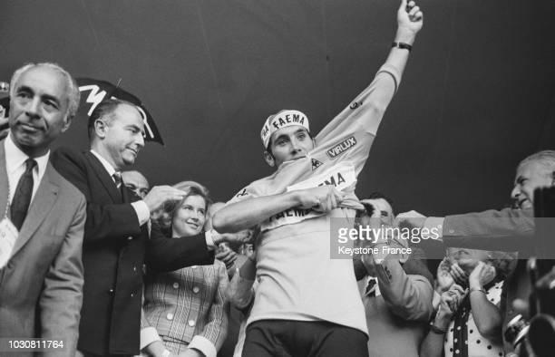 Eddy Merckx, au côté de sa femme, enfile le maillot jaune de vainqueur du Tour de France 69 à Vincennes en juillet 1969, en France.