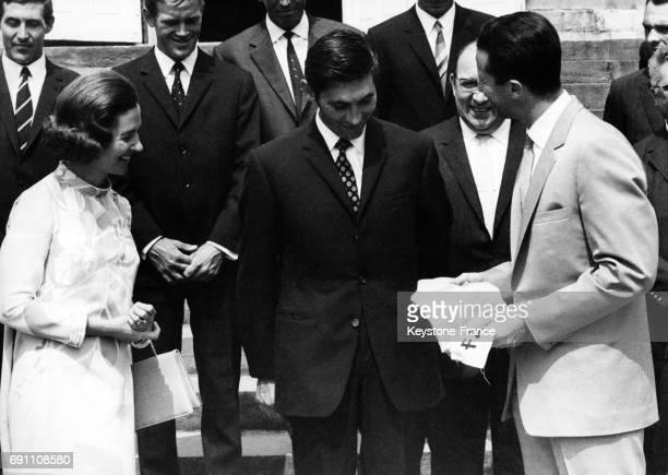 Eddy Merckx vainqueur du Tour de France offre son maillot jaune au roi Baudouin à gauche la Reine Fabiola à Bruxelles Belgique le 22 juillet 1969