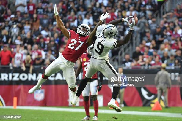 Eddy Pineiro of the Oakland Raiders makes a catch in front of Leonard Johnson of the Arizona Cardinals in the NFL game at State Farm Stadium on...