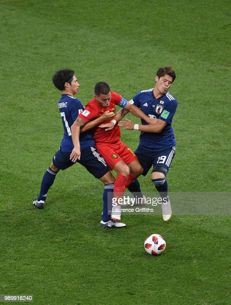 Eden Hazard of Belgium is challenged by Gaku Shibasaki of Japan and Hiroki Sakai of Japan during the 2018 FIFA World Cup Russia Round of 16 match...