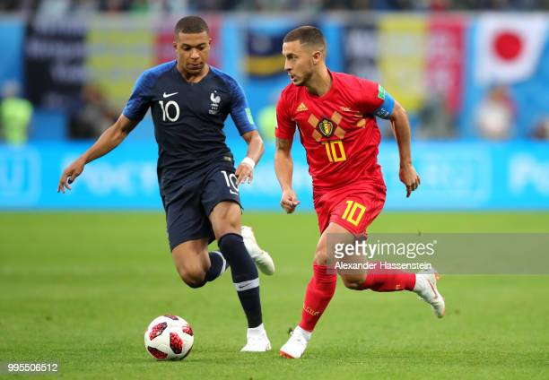 Eden Hazard of Belgium runs with the ball under pressure from Kylian Mbappe of France during the 2018 FIFA World Cup Russia Semi Final match between...