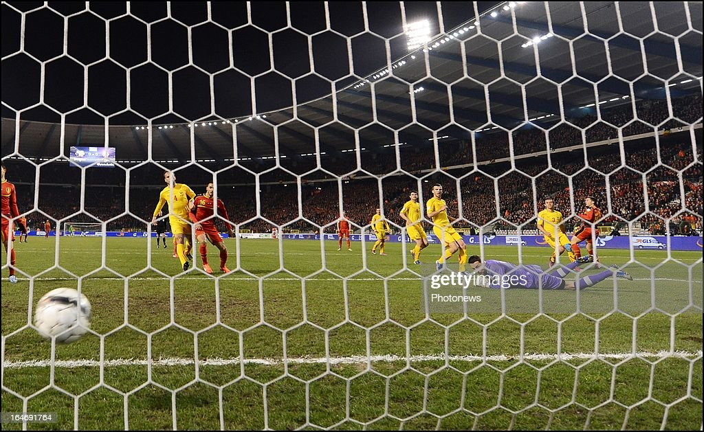 Eden Hazard (R) of Belgium scores the opening goal past Tomislav Pacovski of Macedonia during the FIFA 2014 World Cup Group A qualifying match between Belgium and Macedonia at the King Baudouin stadium on March 26, 2013 in Brussels, Belgium