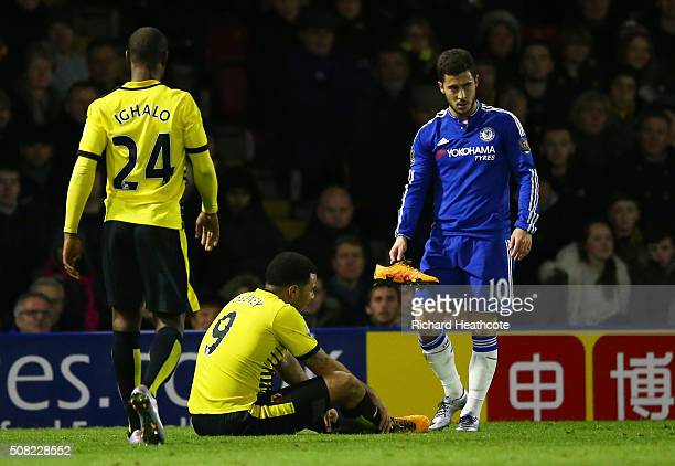 Eden Hazard of Chelsea assists Troy Deeney of Watford with his lost boot during the Barclays Premier League match between Watford and Chelsea at...