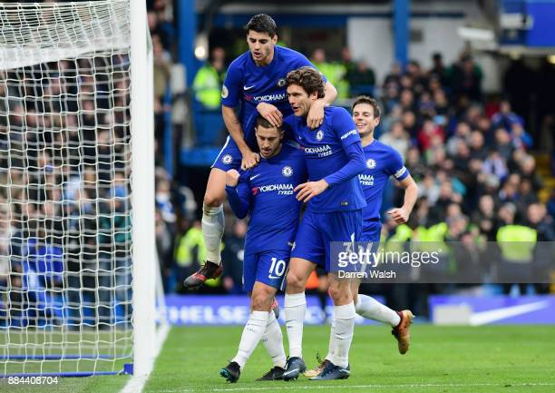 Eden Hazard of Chelsea celebrates after scoring his sides third goal with his Chelsea team mates during the Premier League match between Chelsea and...