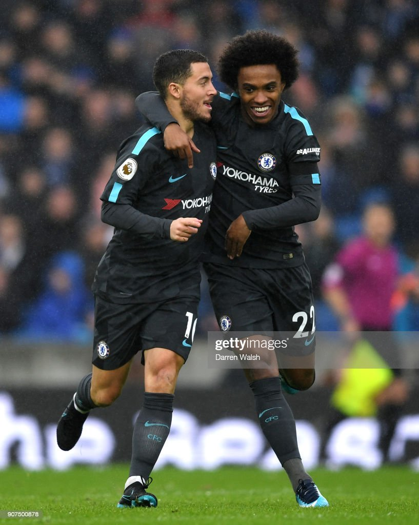 Eden Hazard of Chelsea (L) celebrates as he scores their first goal with team mate Willian during the Premier League match between Brighton and Hove Albion and Chelsea at Amex Stadium on January 20, 2018 in Brighton, England.