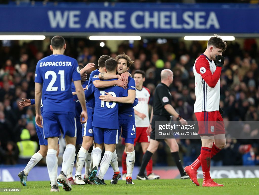 Eden Hazard of Chelsea (10) celebrates scoring their 3rd goal with Cesc Fabregas of Chelsea and the rest of the team beneath a We Are Chelsea banner during the Premier League match between Chelsea and West Bromwich Albion at Stamford Bridge on February 12, 2018 in London, England.