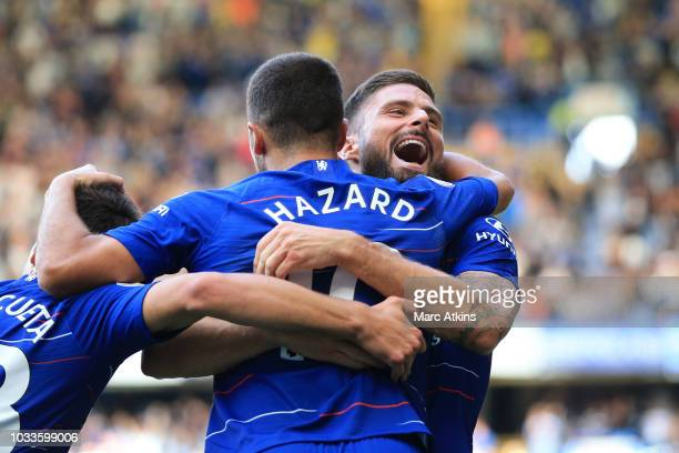 Eden Hazard of Chelsea celebrates with teammate Olivier Giroud after scoring his team's first goal during the Premier League match between Chelsea FC...