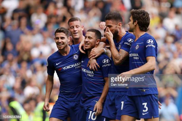 Eden Hazard of Chelsea celebrates with teammates after scoring his team's third goal from a penalty during the Premier League match between Chelsea...