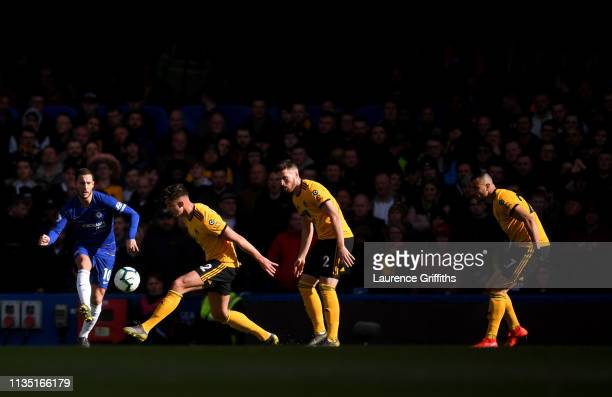 Eden Hazard of Chelsea crosses the ball under pressure from the Wolverhampton Wanderers defence during the Premier League match between Chelsea FC...