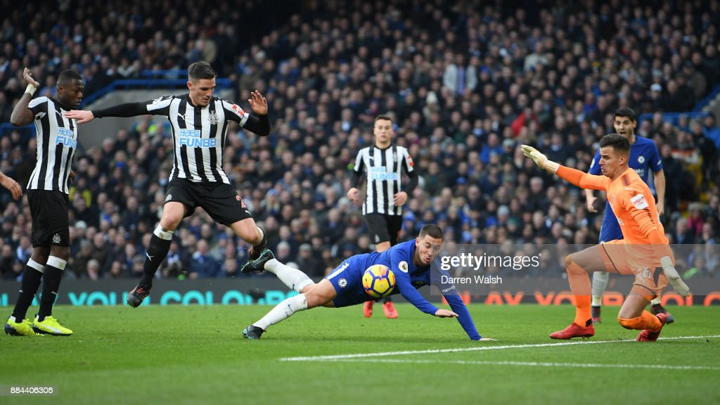 Eden Hazard of Chelsea goes down under the challenge of Ciaran Clark of Newcastle United during the Premier League match between Chelsea and Newcastle United at Stamford Bridge on December 2, 2017 in London, England.