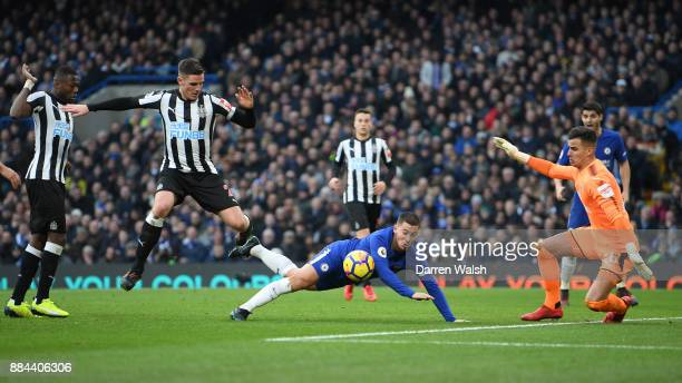 Eden Hazard of Chelsea goes down under the challenge of Ciaran Clark of Newcastle United during the Premier League match between Chelsea and...