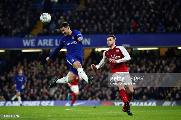 Eden Hazard of Chelsea heads the ball away from Calum Chambers of Arsenal during the Carabao Cup SemiFinal First Leg match between Chelsea and...