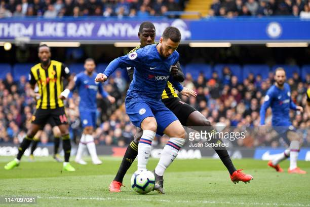 Eden Hazard of Chelsea holds off Abdoulaye Doucoure of Watford during the Premier League match between Chelsea FC and Watford FC at Stamford Bridge...