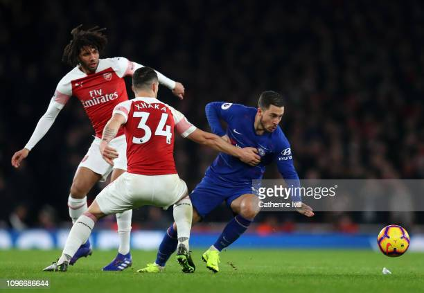 Eden Hazard of Chelsea is challenged by Granit Xhaka and Mohamed Elneny of Arsenal during the Premier League match between Arsenal FC and Chelsea FC...