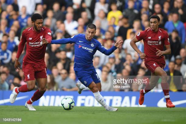 Eden Hazard of Chelsea is challenged by Joe Gomez and Trent AlexanderArnold of Liverpool during the Premier League match between Chelsea FC and...