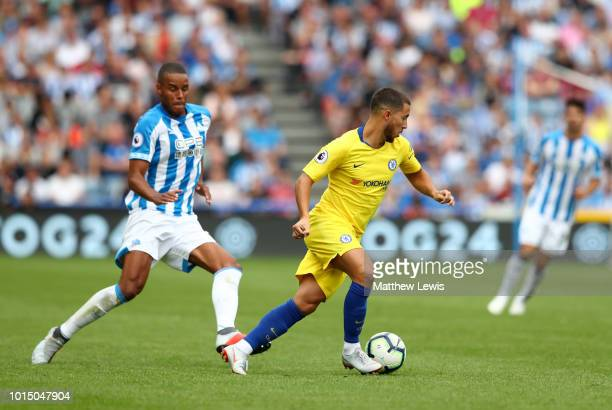 Eden Hazard of Chelsea is challenged by Mathias Zanka Jorgensen of Huddersfield Town during the Premier League match between Huddersfield Town and...